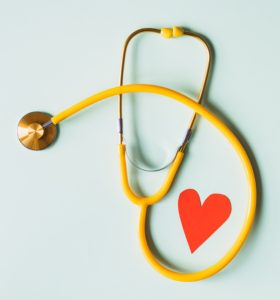 Yellow stethoscope with a red paper heart beside it and a light mint background.