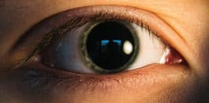 This is a person's eye with a green iris and very large, dilated pupil.