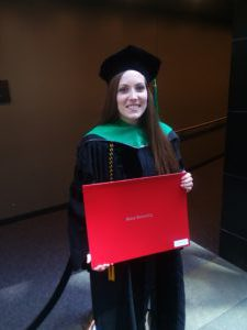 Woman in black and green cap and gown holding a red diploma folder
