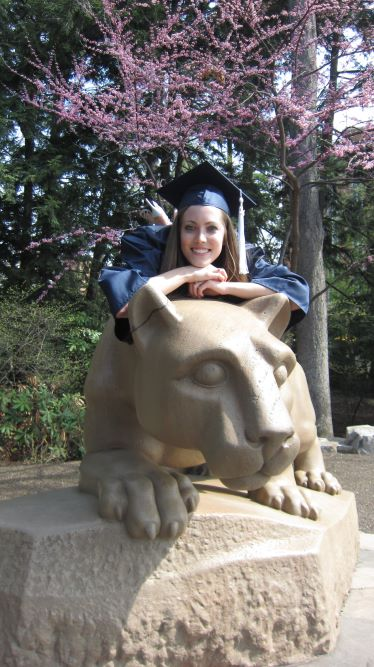 Girl in graduation cap and gown on the Penn State Nittany Lion Shrine
