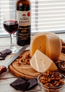 Large wheel of cheese with a wedge cut out. There is a glass of red wine with the bottle. Scattered nuts and chocolate cover the wooden cheese board.