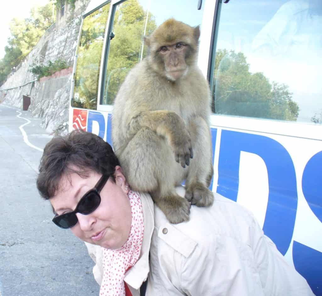 Woman wearing white coat and sunglasses with a monkey on her back